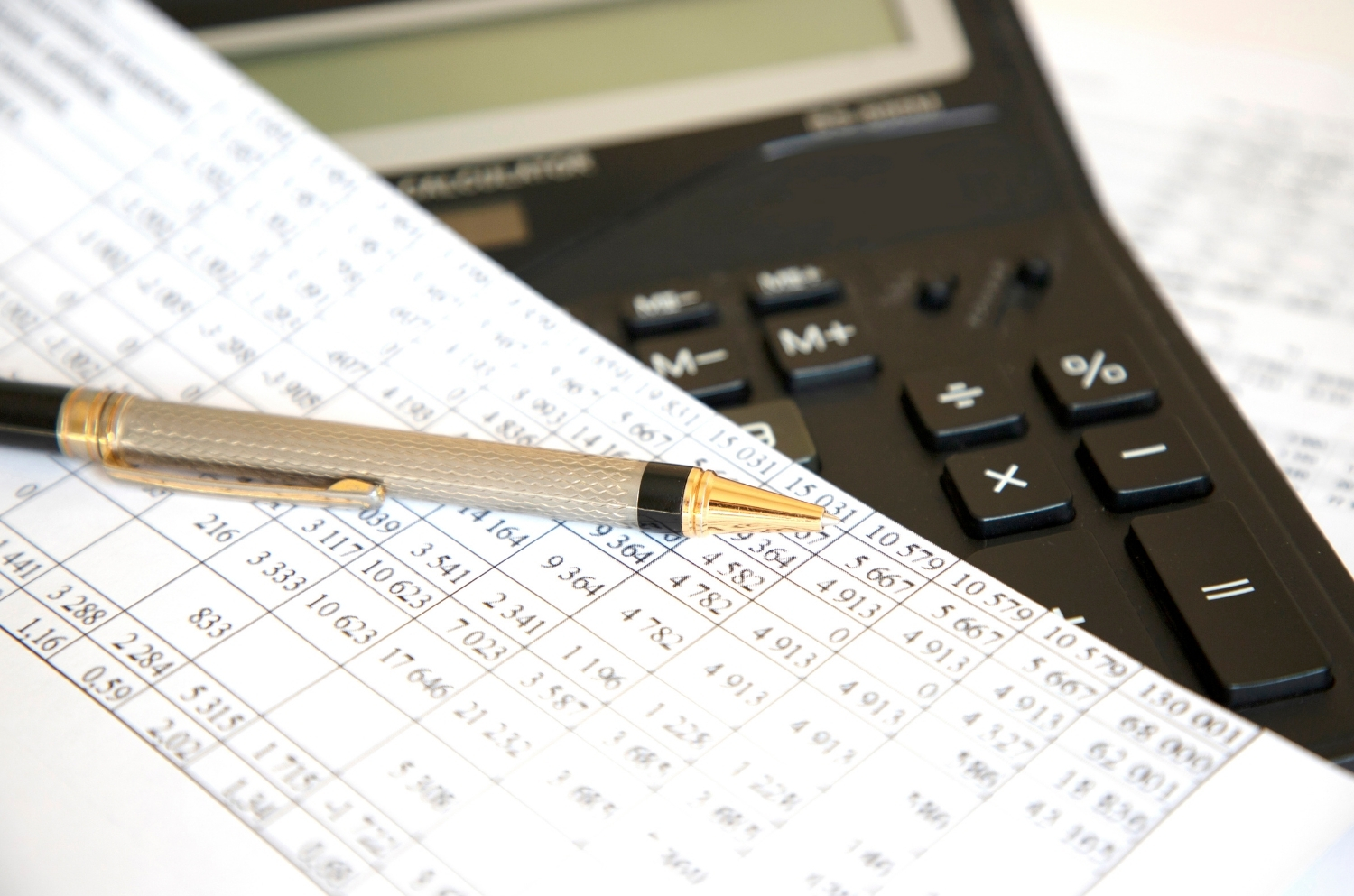 picture of spreadsheet and calculator - property analyzation by commercial real estate broker
