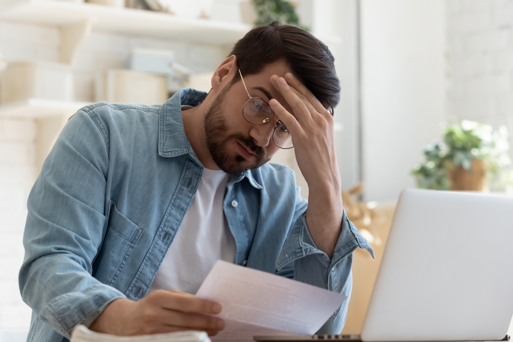 man at computer looking at numbers, concerned about a commercial property foreclosure